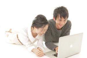 PCを見ているカップル